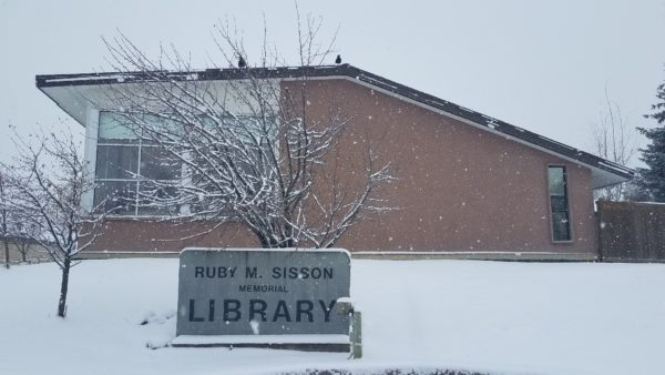 The Ruby M. Sisson Library building and sign, during a snowstorm.
