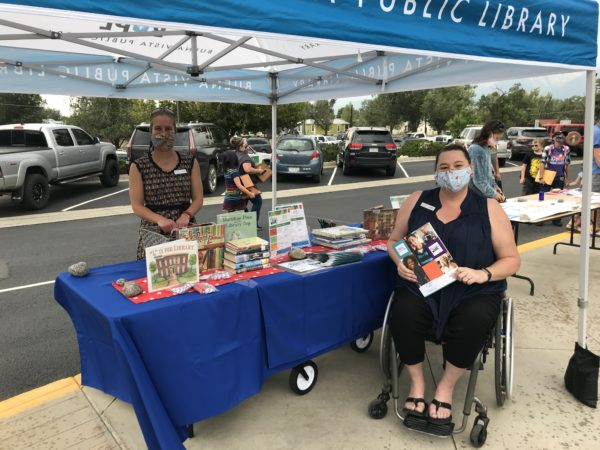 Library staff, one standing and one seated in a wheelchair, work at the library's table on the sidewalk at back to school night during the COVID-19 pandemic.