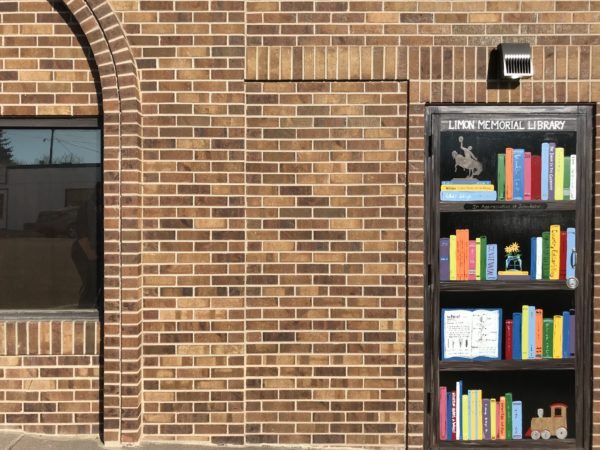The side door of the Limon Public Library, painted to look like a book shelf with colorful titles on display.