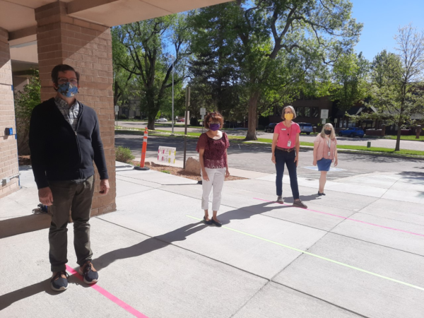Longmont Public Library Staff stand outside the library, aligned with ground marking indicating safe social distancing.