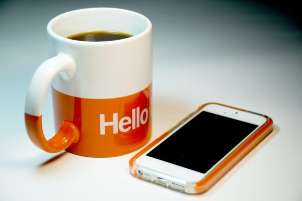 """An iphone sits on a white table next to a n orange and white coffee mug with the word """"Hello"""" inscribed on it."""